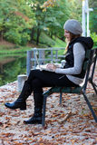 Woman sitting on a bench with her Laptop. Next to a river Royalty Free Stock Image
