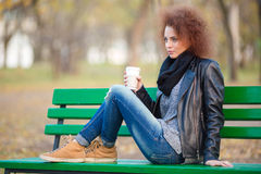 Woman sitting on the bench and holding cup with coffee Royalty Free Stock Image