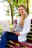Woman sitting on bench with laptop Royalty Free Stock Photography