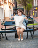 Woman sitting on bench and looking inside of white paper bag aft Royalty Free Stock Image