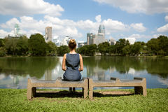 Woman sitting on a bench and looking at lake in city park stock image