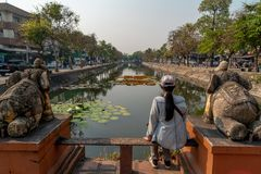 Woman is sitting on the bench and looking at the moat of Chiang Mai. stock photography