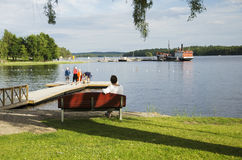 Woman sitting on a bench looking out on the lake. In Savonlinna, Finland Royalty Free Stock Photography