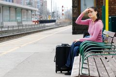 Woman sitting on bench looking for the train Royalty Free Stock Photo