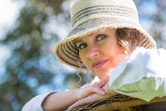 Woman sitting  on a bench in  nature. Woman in hat sitting on a wicker bench in the garden Royalty Free Stock Images