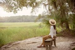 Woman Sitting on Bench Near Forest and Grass royalty free stock photos