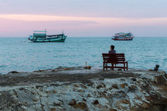 Woman sitting on a bench near the sea in the evening. Royalty Free Stock Photos