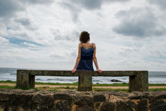 Woman sitting on bench near sea, horizontal Royalty Free Stock Photos