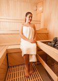 Woman sitting on bench next to sauna oven Stock Photo