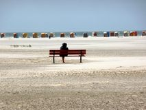 Woman sitting on a bench at North Sea beach Royalty Free Stock Photo