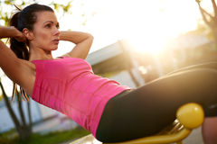 Woman sitting on bench outside doing situps. Stock Photo