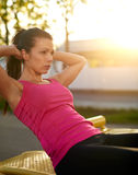 Woman sitting on a bench outside doing situps Stock Photography