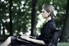 Woman sitting on a bench in park Royalty Free Stock Image
