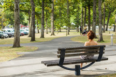 Woman sitting on a bench in the park Stock Photo