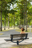 Woman sitting on a bench in the park Stock Image