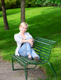 Woman sitting on bench in park vertical Stock Image