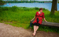 Woman sitting on bench by a pond in the park Royalty Free Stock Image