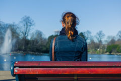 Woman sitting on bench by pond Royalty Free Stock Photos
