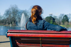 Woman sitting on bench by pond Royalty Free Stock Images