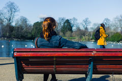 Woman sitting on bench by pond Royalty Free Stock Photo