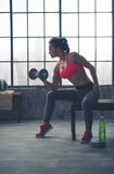 Woman sitting on bench in profile lifting weights in loft gym Royalty Free Stock Photography