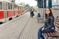 Woman sitting on a bench in a railway station Royalty Free Stock Images