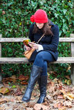 Woman Sitting On A Bench And Reading A Book. Clothed in warm winter clothing Royalty Free Stock Images