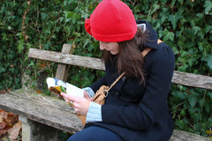 Woman Sitting On A Bench And Reading A Book. Clothed in warm winter clothing Stock Photo