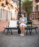 Woman sitting on bench with shopping bags and using tablet Royalty Free Stock Images