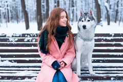 Woman sitting on the bench with siberian husky Stock Photo