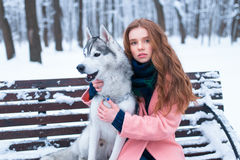 Woman sitting on the bench with siberian husky Royalty Free Stock Image