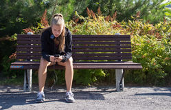 Woman sitting on a bench with smart phone Stock Images