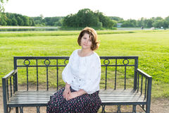 Woman sitting on bench in summer park Stock Photo