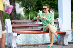 Woman sitting on a bench and talking on the phone Stock Images