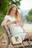 Woman sitting on a bench talking on the phone fun in the summer Stock Photo