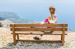 Woman sitting on bench on top of mountain Royalty Free Stock Images