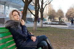 Woman sitting on a bench in an urban park Royalty Free Stock Photos