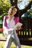 Woman sitting on bench and using digital tablet in garden Stock Images