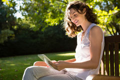 Woman sitting on bench and using digital tablet in garden on a sunny day Stock Image