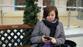 Woman sitting on bench and using her smartphone stock footage