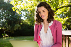 Woman sitting on bench and using laptop in garden on a sunny day. Smiling woman sitting on bench and using laptop in garden on a sunny day Royalty Free Stock Images