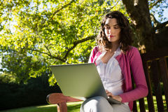 Woman sitting on bench and using laptop in garden on a sunny day. Smiling woman sitting on bench and using laptop in garden on a sunny day Stock Photos
