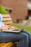 Woman sitting on bench using laptop Stock Image
