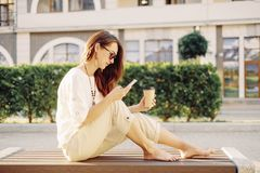 Woman sitting on bench and using mobile phone. Beautiful brunette barefoot young woman sitting with cup of paper coffee on wooden bench and using mobile phone stock image