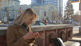 Woman sitting on bench using smart mobile phone reading at sunny city street stock footage