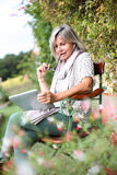 Woman sitting on bench websurfing from garden Stock Photo