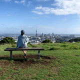 Woman sitting on bench will looking at skyline of Auckland Stock Images