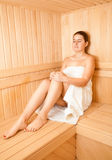 Woman sitting on bench at wooden traditional sauna Stock Photos