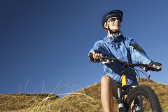 Woman Sitting On Bicycle In Field Royalty Free Stock Photos