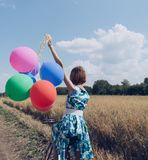 Woman sitting on bicycle and holding balloons stock images